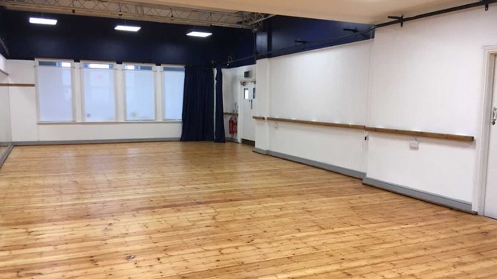 Studio with mirrored walls, blackout curtain, lighting truss and sound equipment